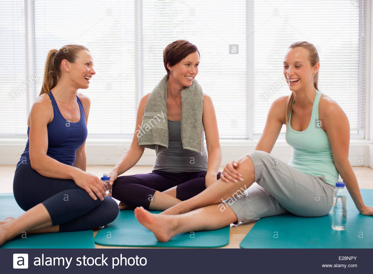Smiling women resting on exercise mats - Stock Image