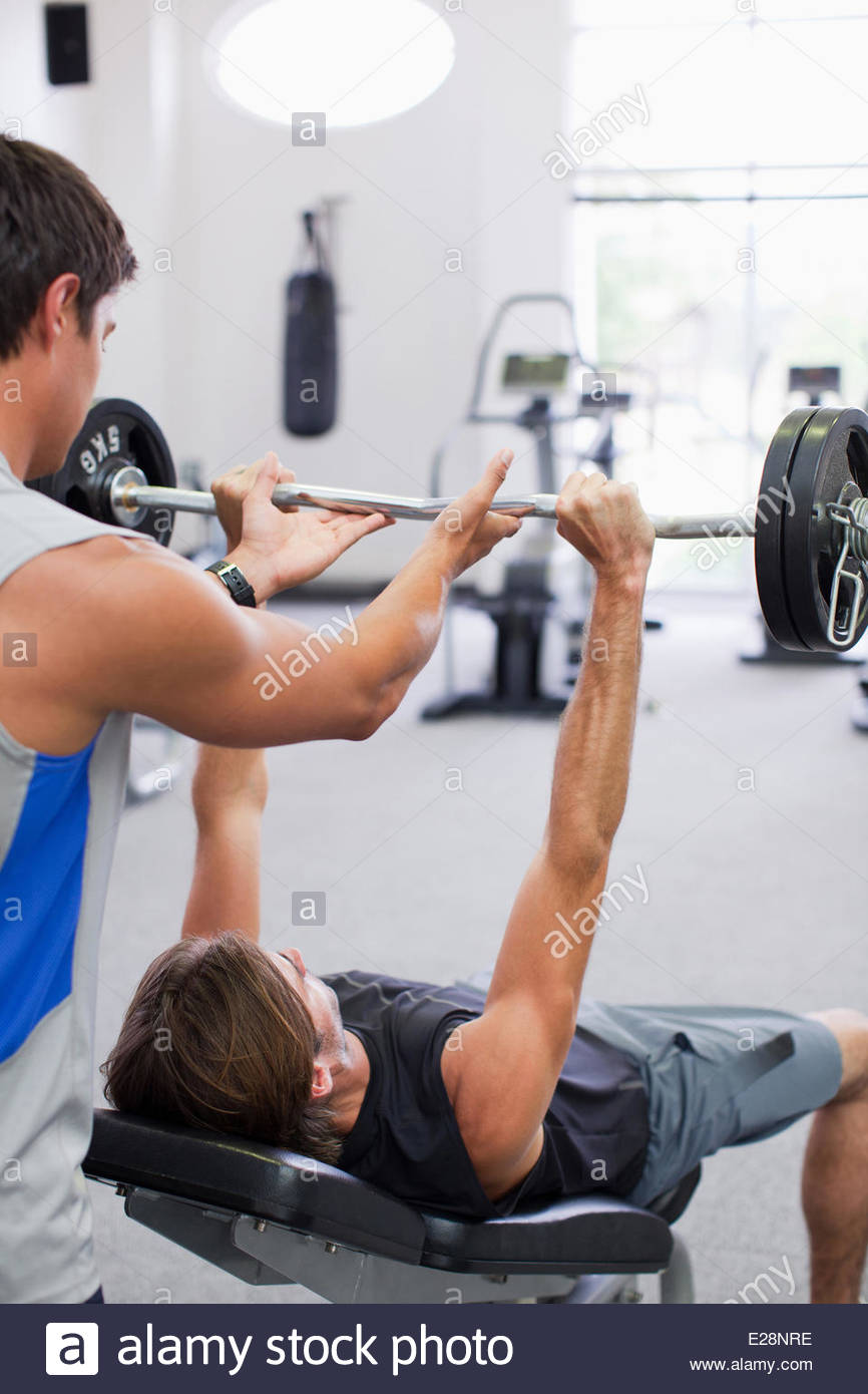 Man spotting friend lifting barbell in gymnasium - Stock Image