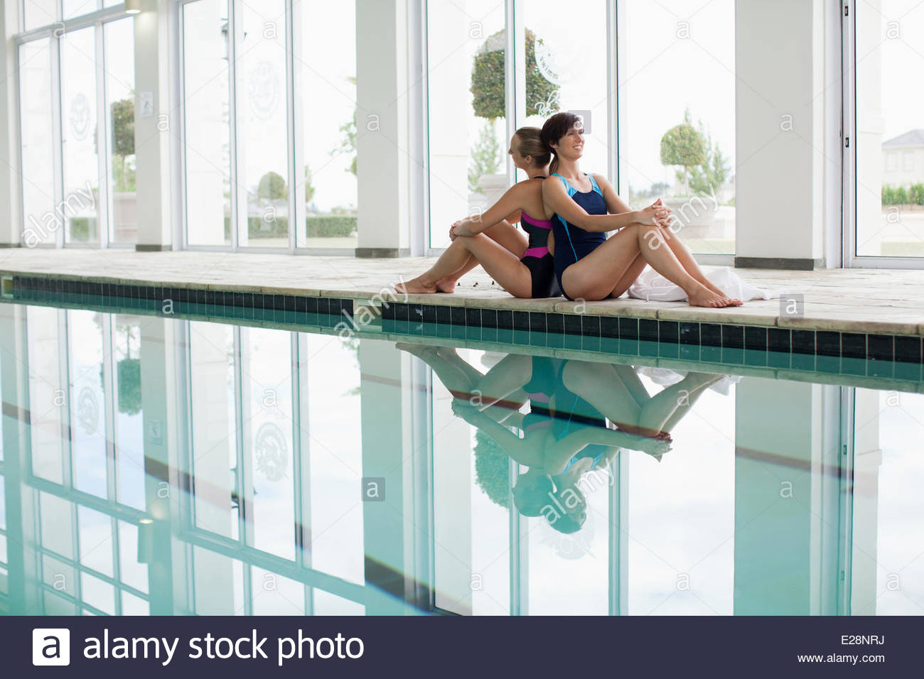 Two women in bathing suits sitting poolside - Stock Image