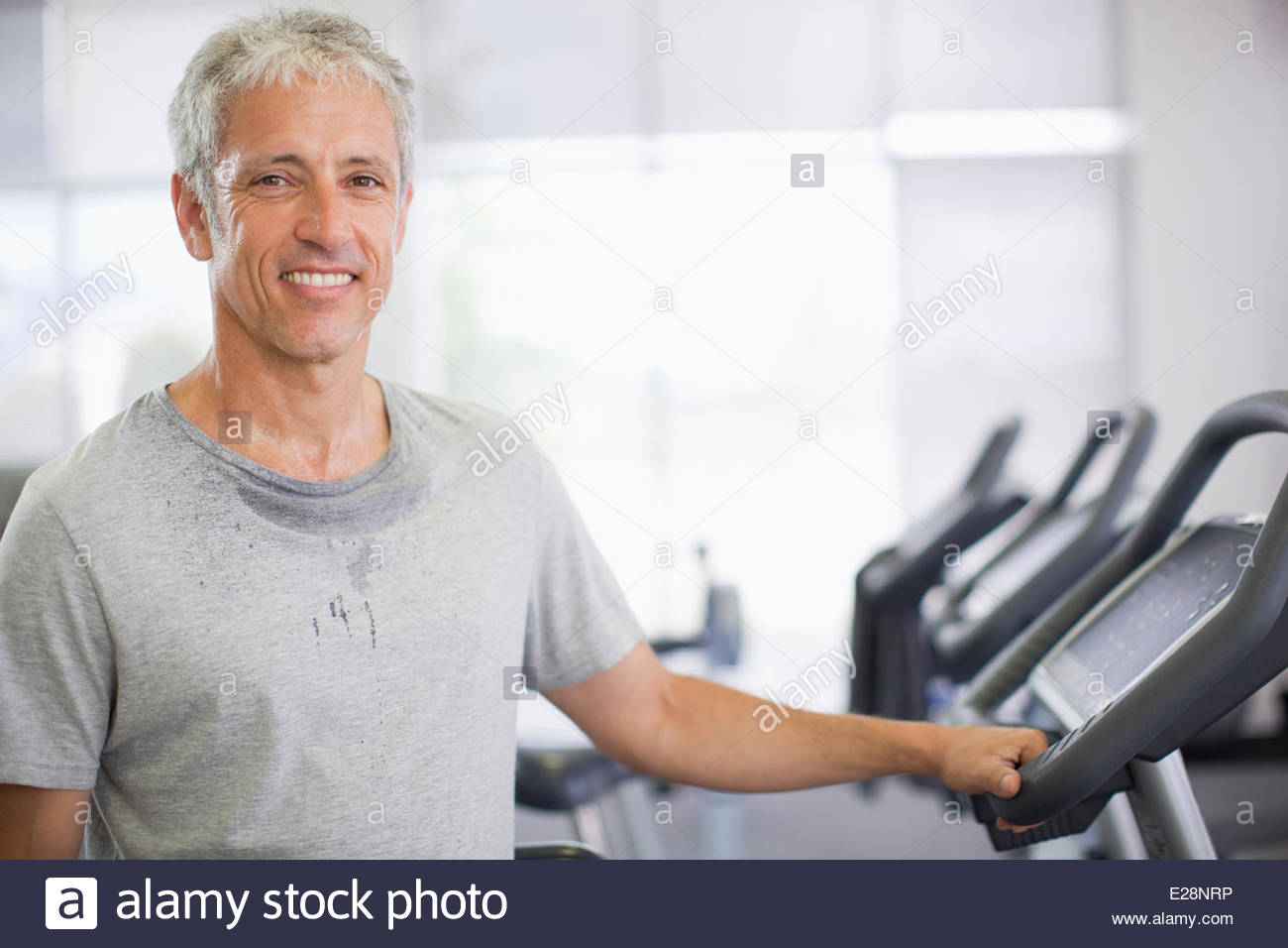 Portrait of smiling man on treadmill in gymnasium - Stock Image