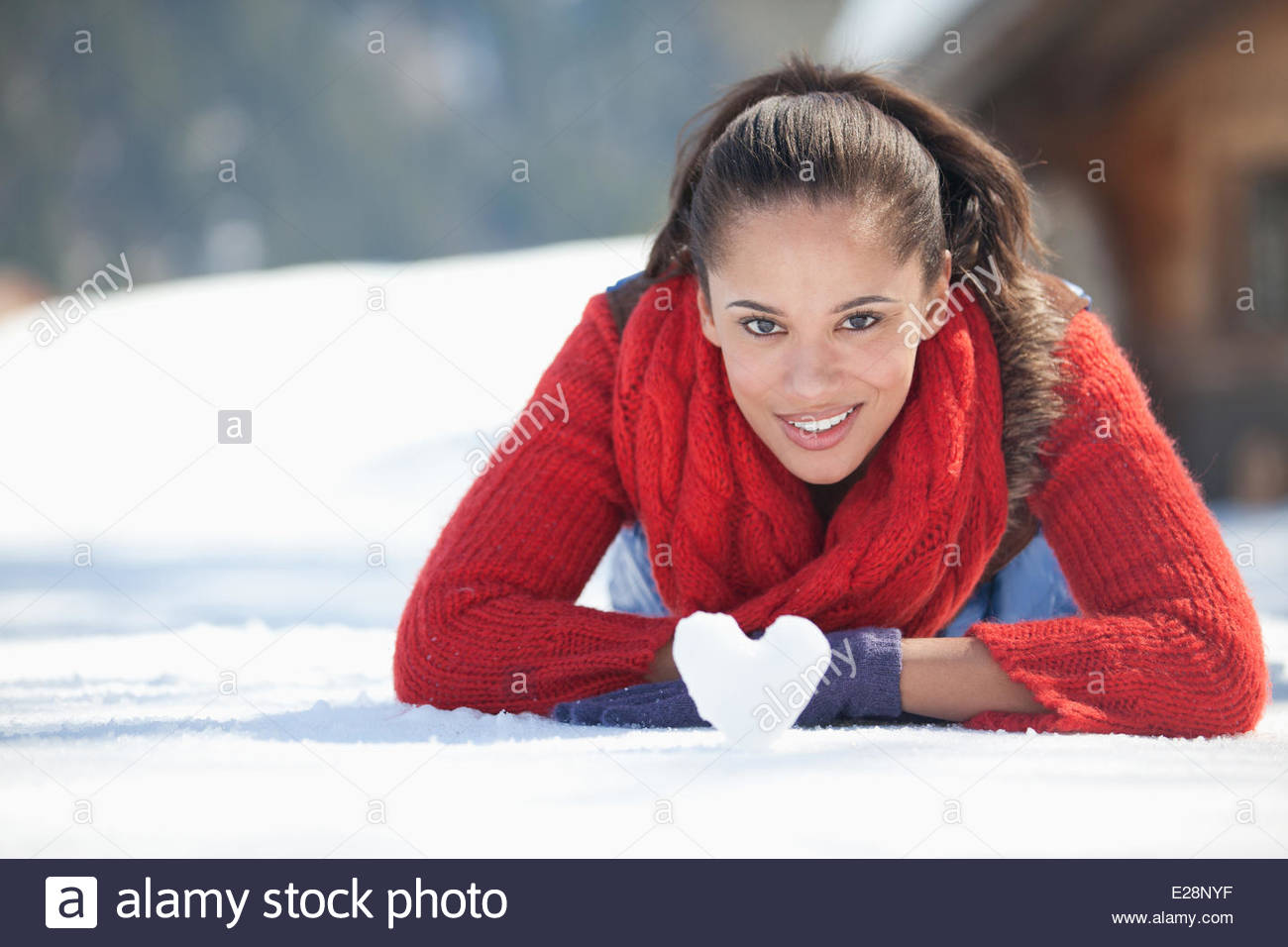 Young woman with heart-shaped snowball - Stock Image