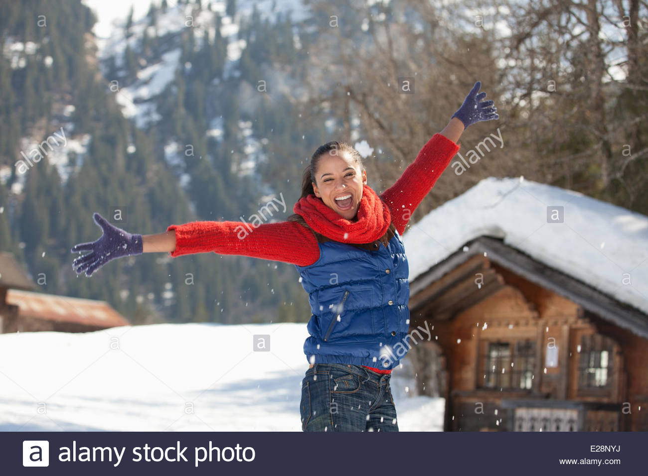 Happy woman throwing snow - Stock Image