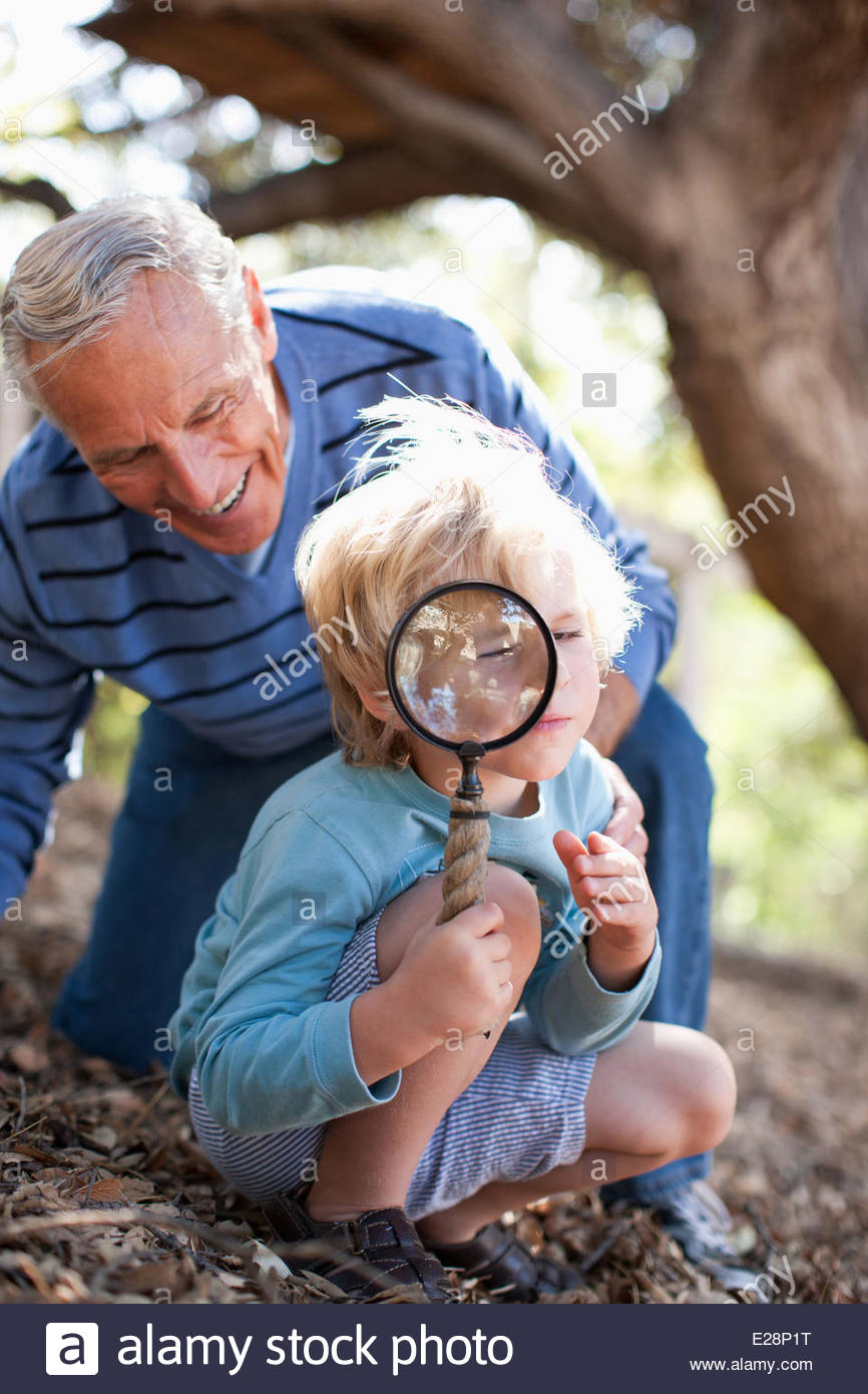 Older man and grandson using magnifying glass - Stock Image