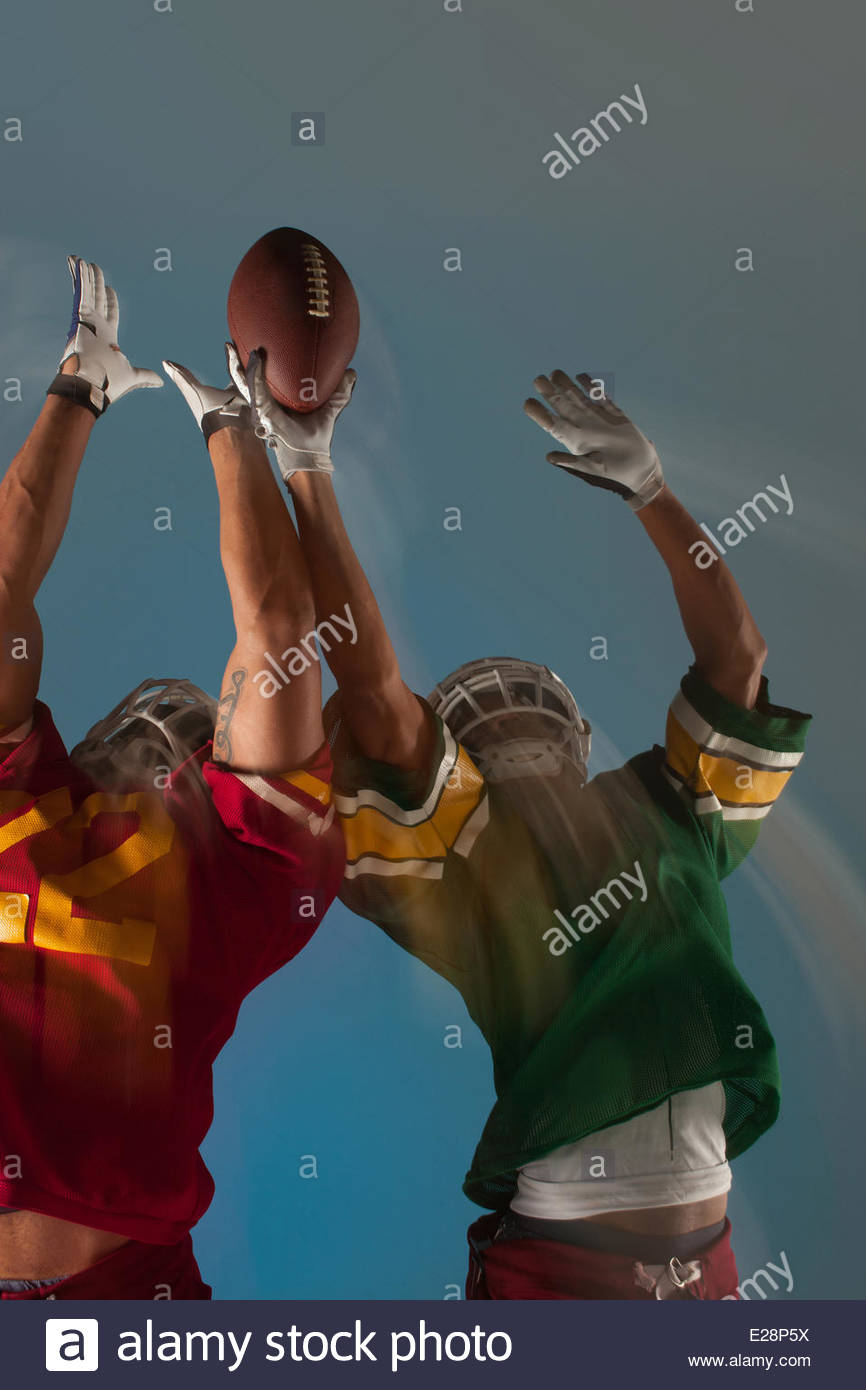 Blurred view of football players reaching for ball - Stock Image