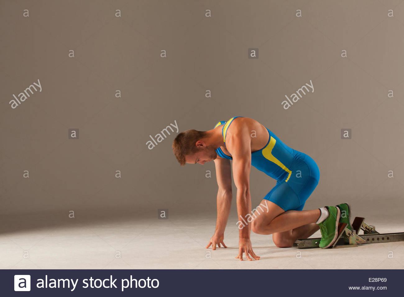 Athlete in starting blocks - Stock Image