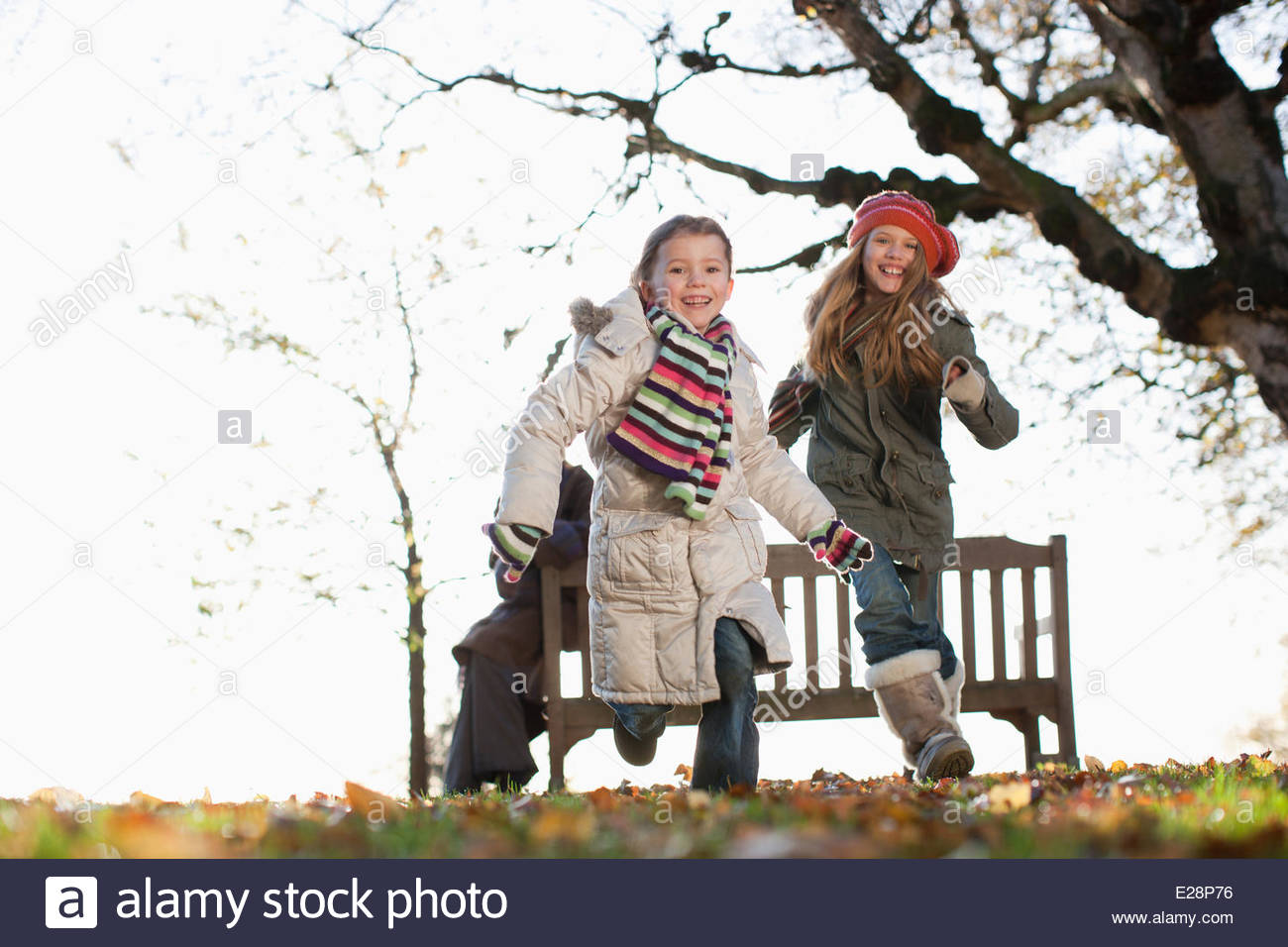 Two sisters playing outdoors in autumn - Stock Image
