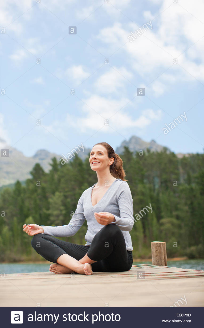 Woman practicing yoga on pier by lake - Stock Image