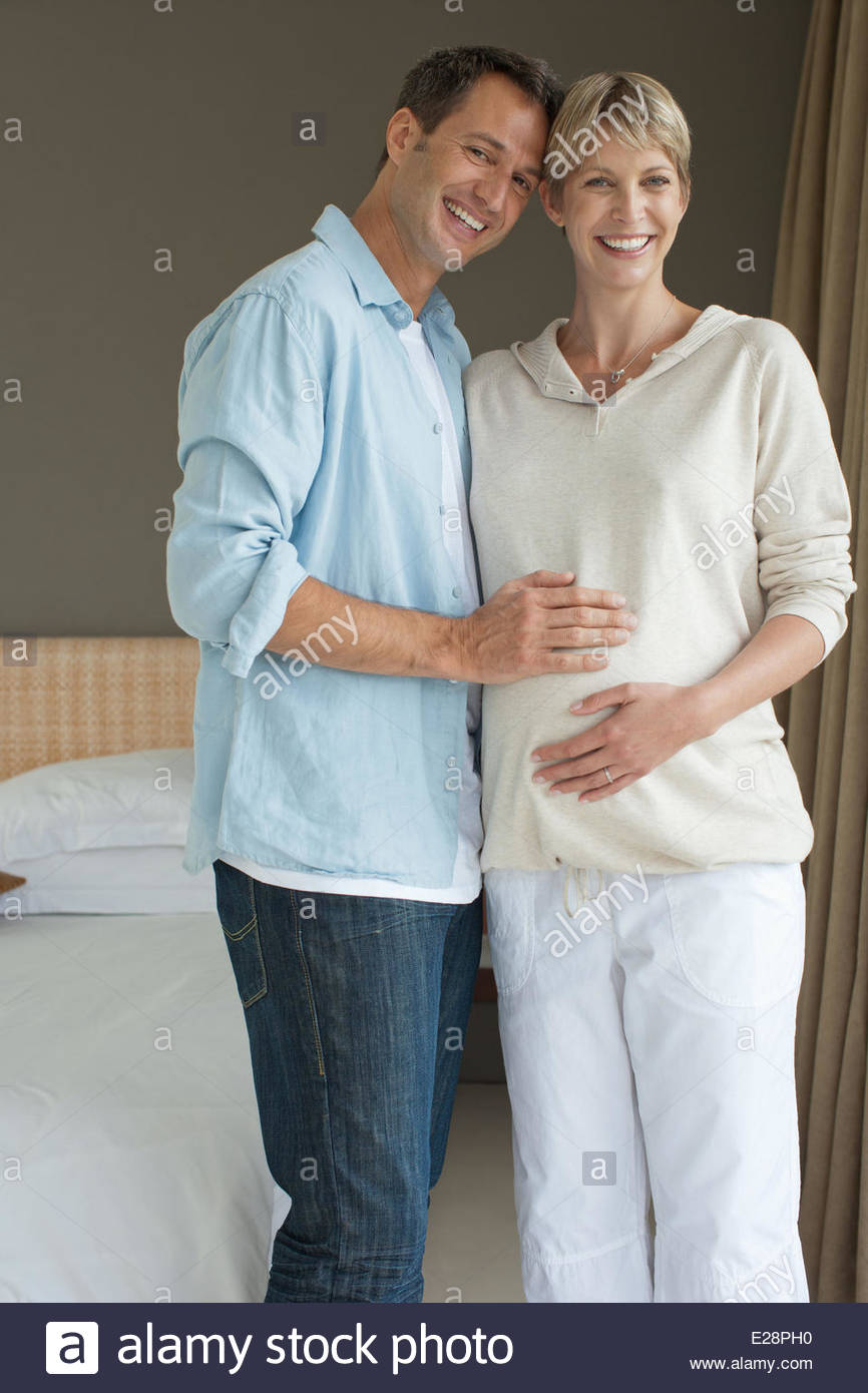Husband touching pregnant wifeÂ's stomach - Stock Image