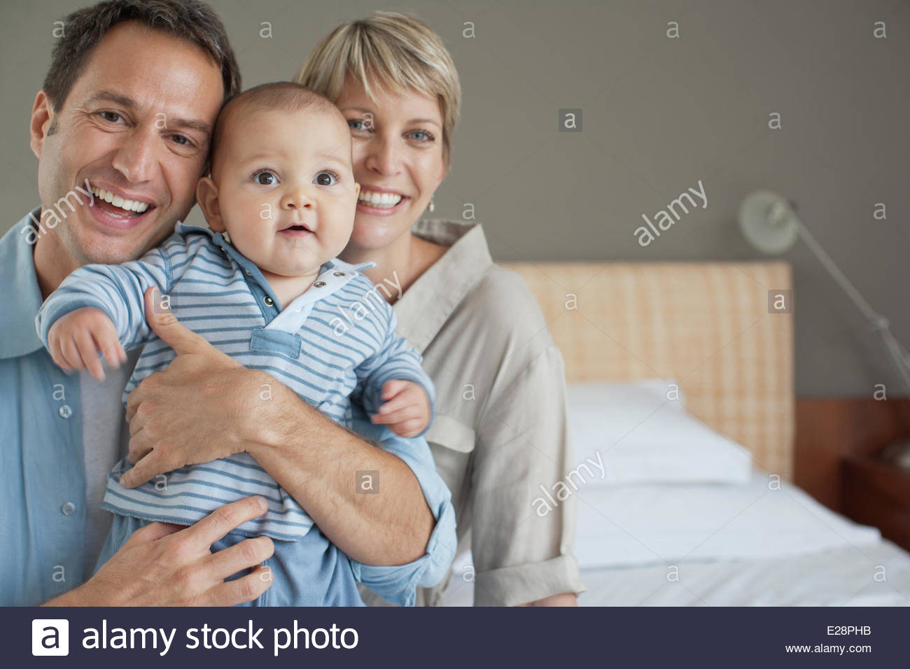 Smiling mother and father with son - Stock Image