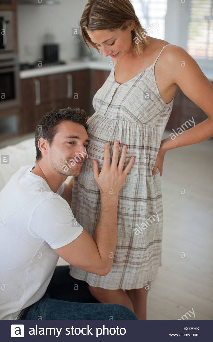 Husband listening to pregnant wifeÂ's stomach - Stock Image