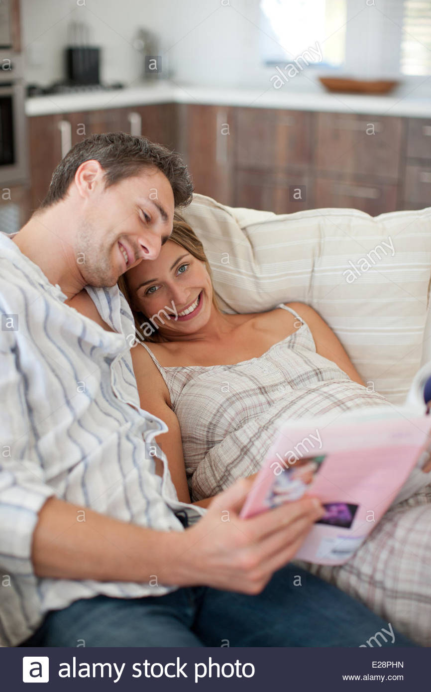 Pregnant woman reading magazine with husband - Stock Image