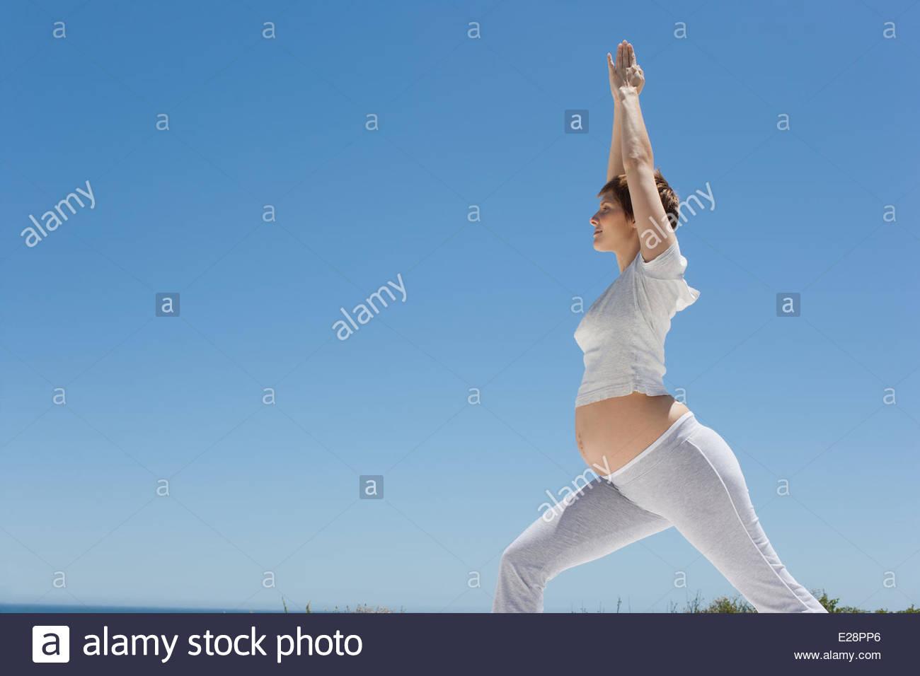 Pregnant woman doing yoga - Stock Image