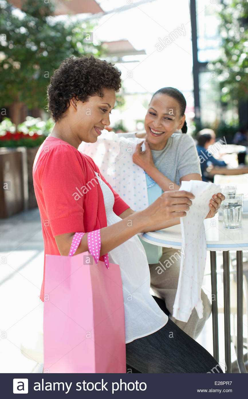 Pregnant woman and friend looking at baby clothes - Stock Image