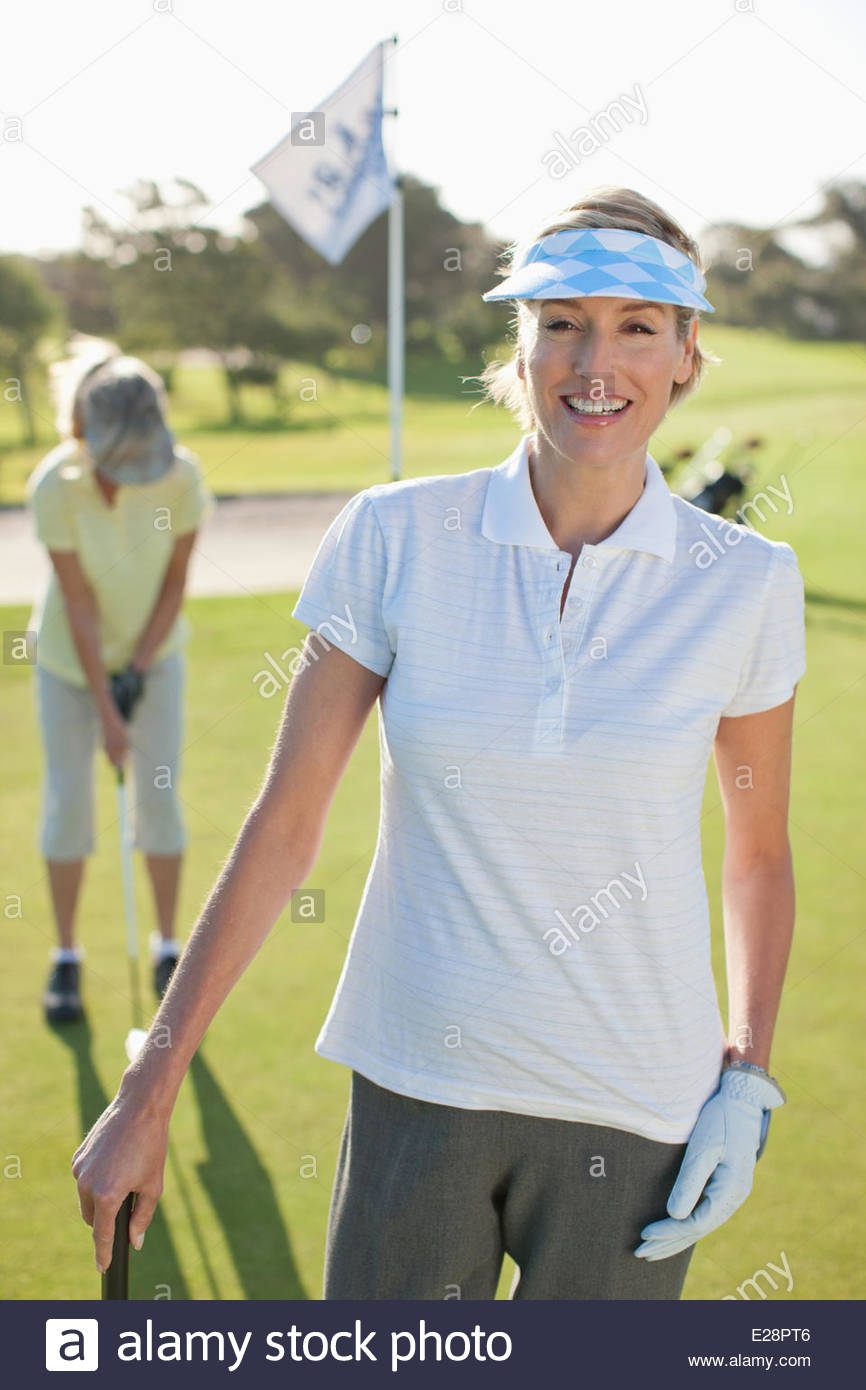 Woman standing on golf course - Stock Image