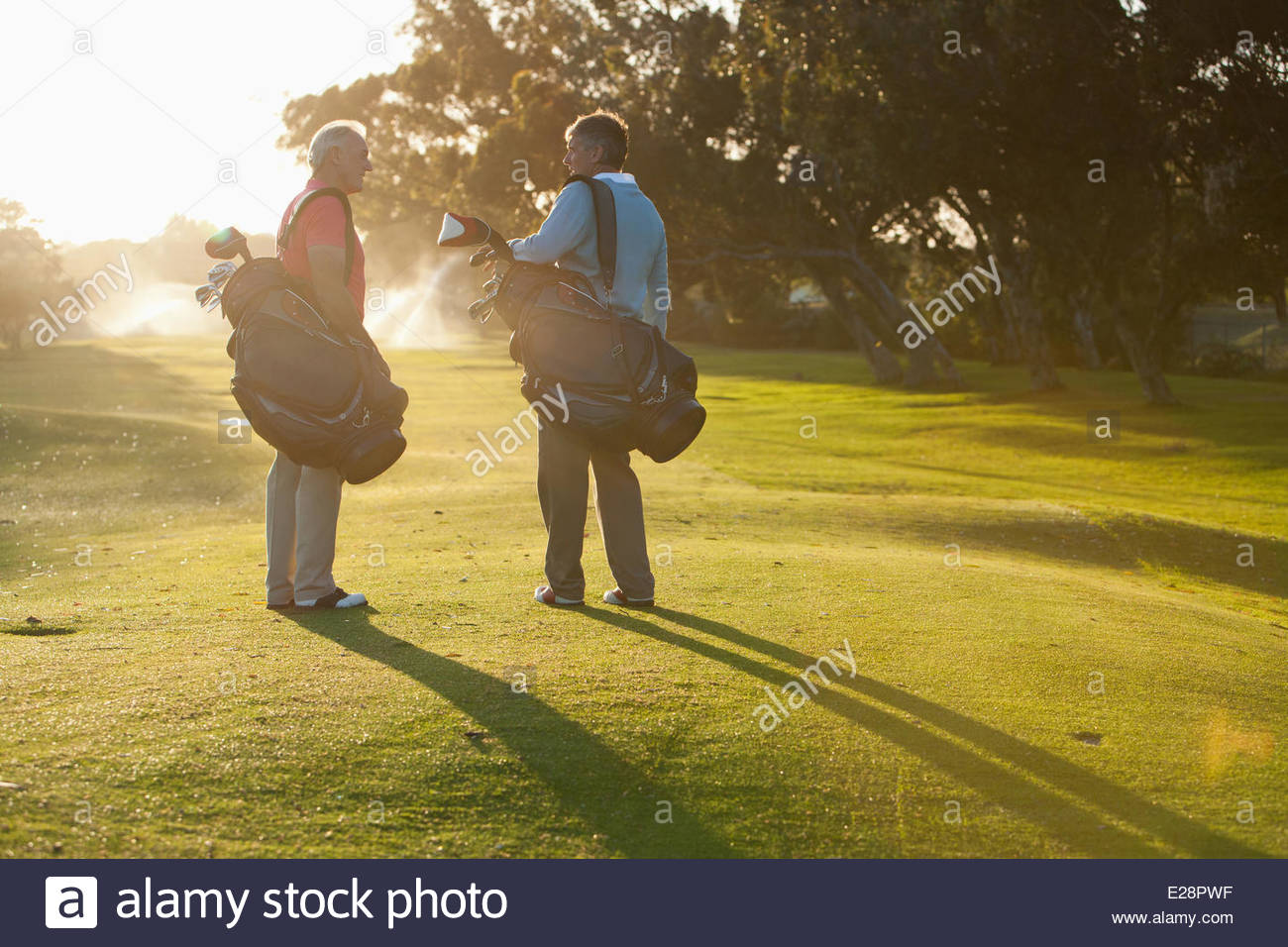 Men carrying golf bags on golf course - Stock Image
