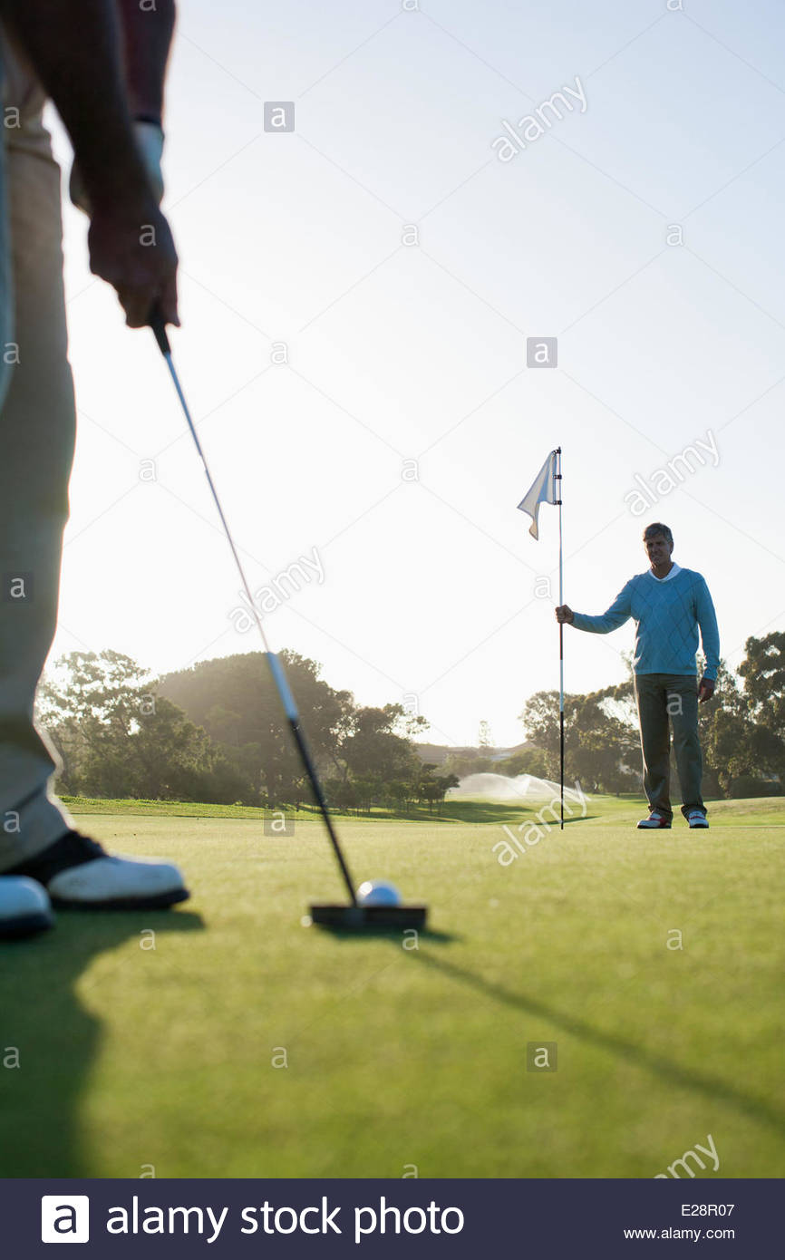 Man putting golf ball - Stock Image