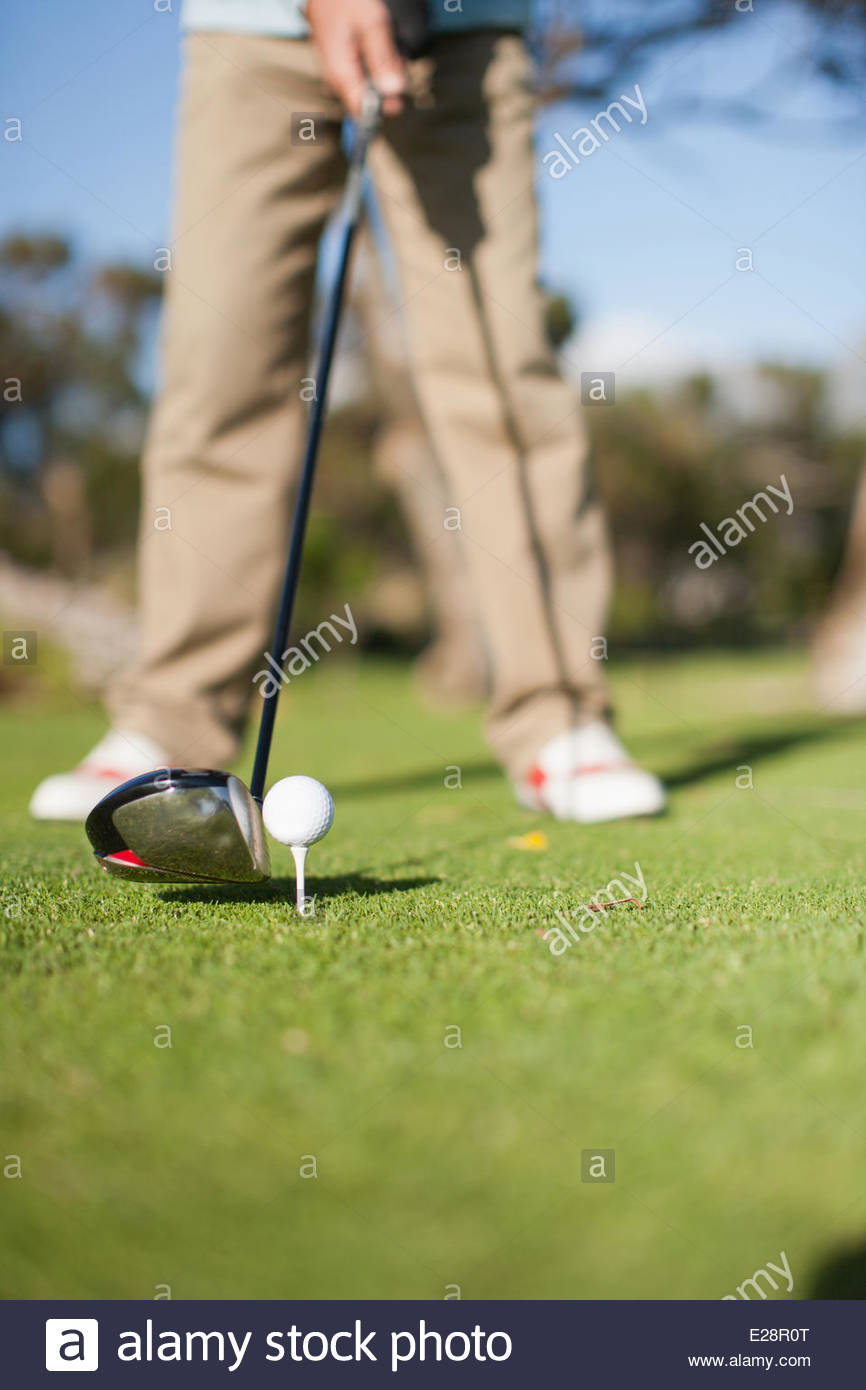 Close up of golf club about to hit golf ball - Stock Image