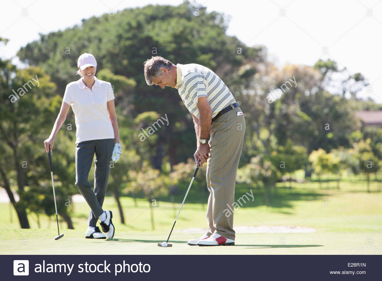 Mature couple playing golf together - Stock Image