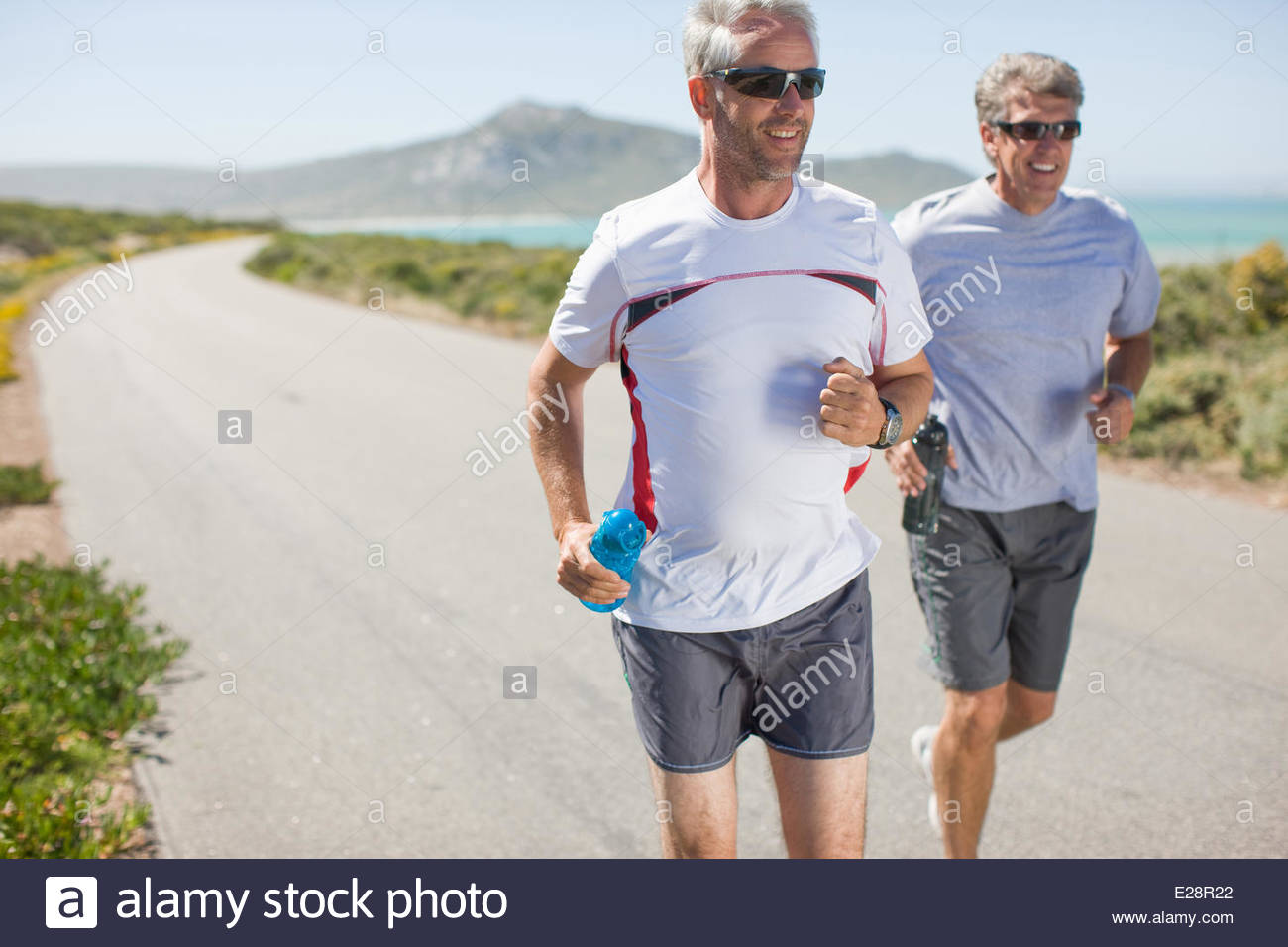 Men jogging and carrying water bottles - Stock Image