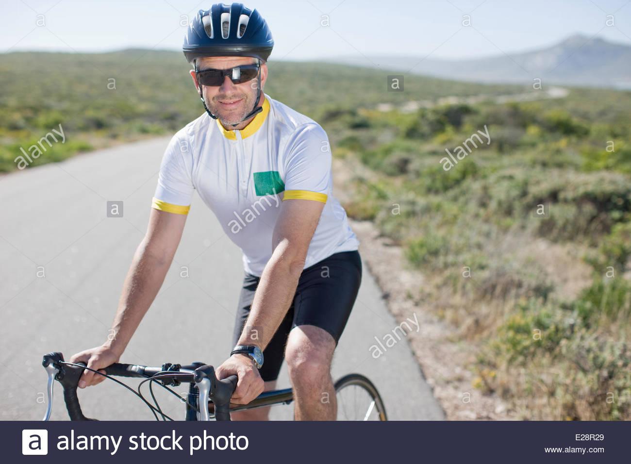 Man in helmet sitting on bicycle - Stock Image