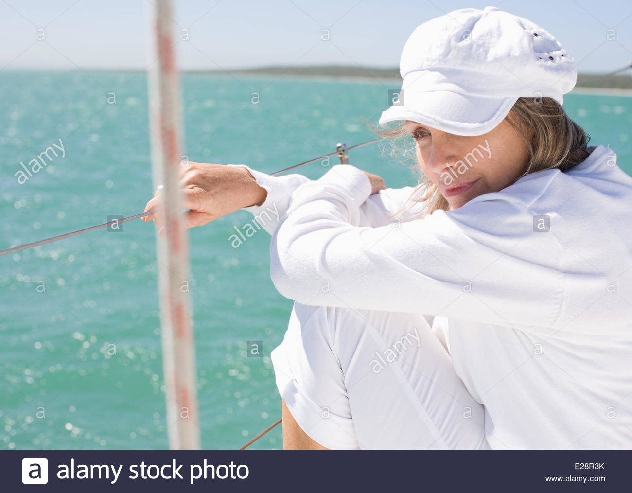 Woman sitting on deck of boat - Stock Image