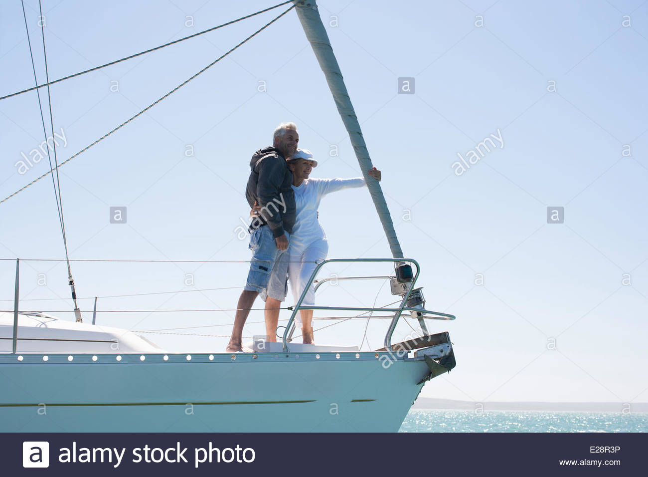 Mature couple hugging on deck of sailboat - Stock Image