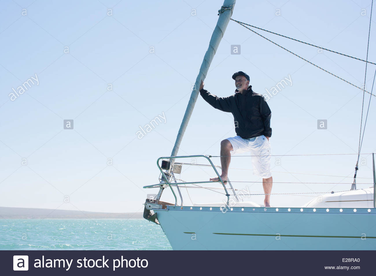 Man standing on deck of sailboat - Stock Image