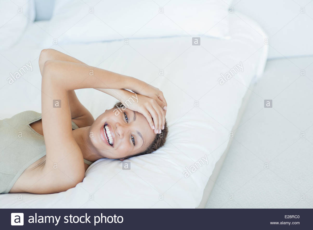 Smiling woman lying on bed - Stock Image