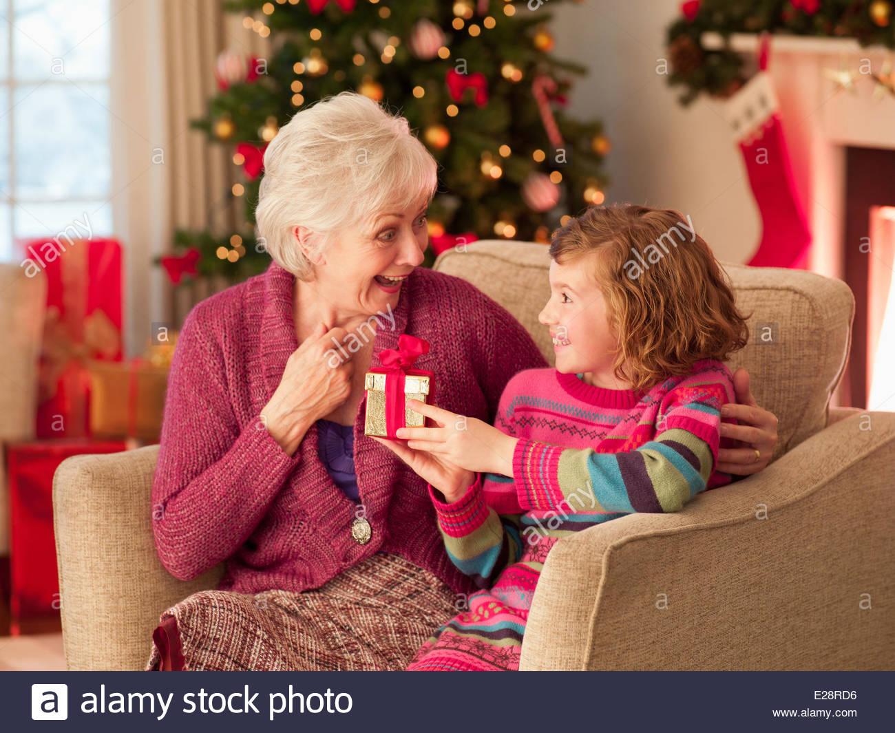 Girl and grandmother holding Christmas gift - Stock Image