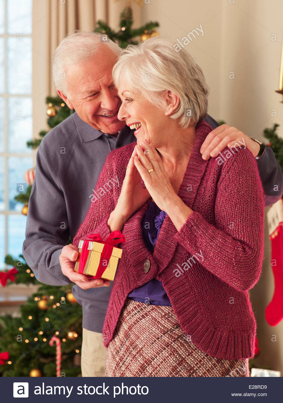 Man surprising woman with Christmas gift - Stock Image