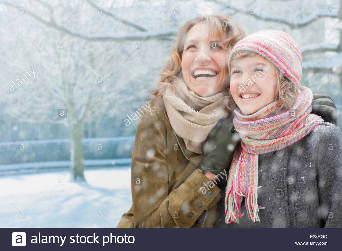 Snow falling on smiling mother and daughter - Stock Image