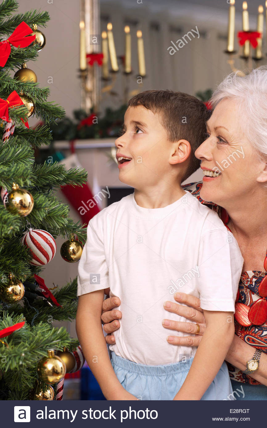 Grandmother and grandson looking Christmas tree - Stock Image