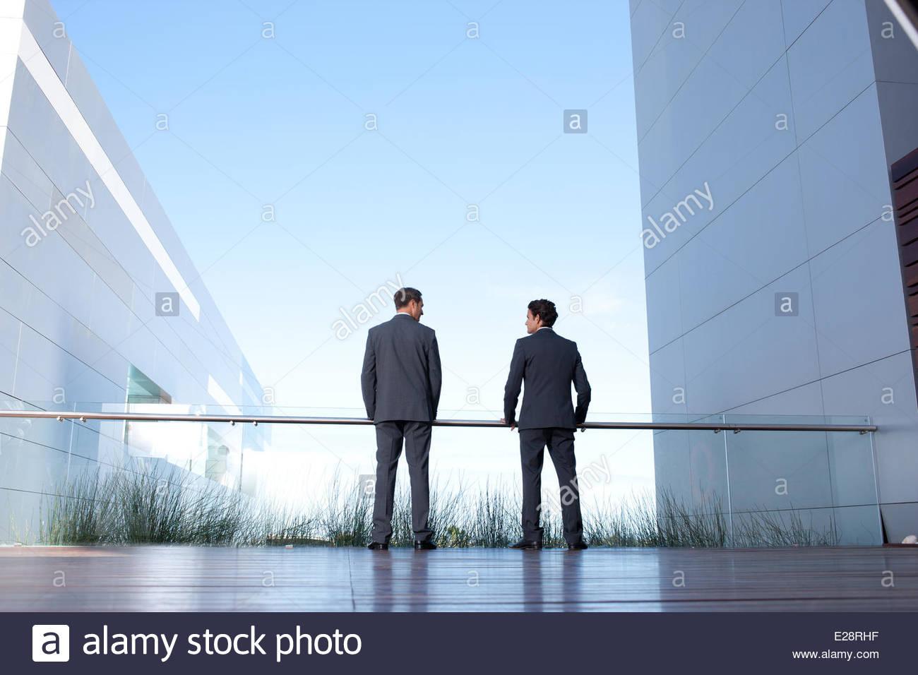 Businessmen standing on balcony - Stock Image