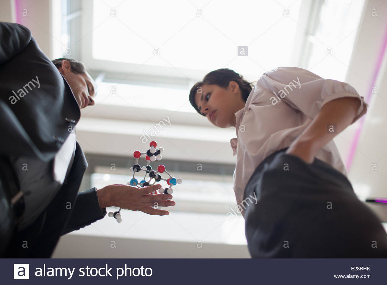 Business people holding model in office - Stock Image