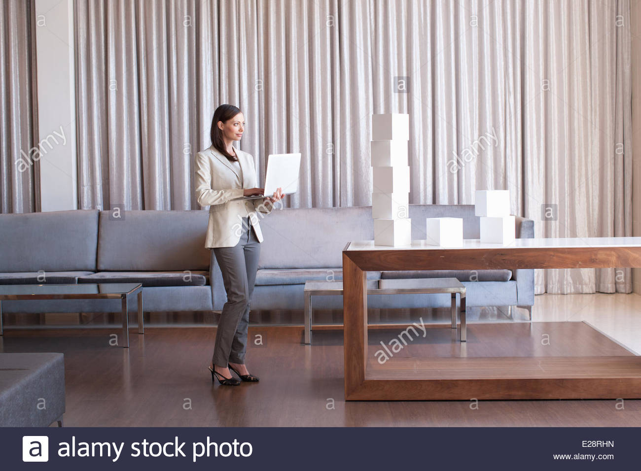 Businesswoman stacking white cubes in hotel lobby - Stock Image