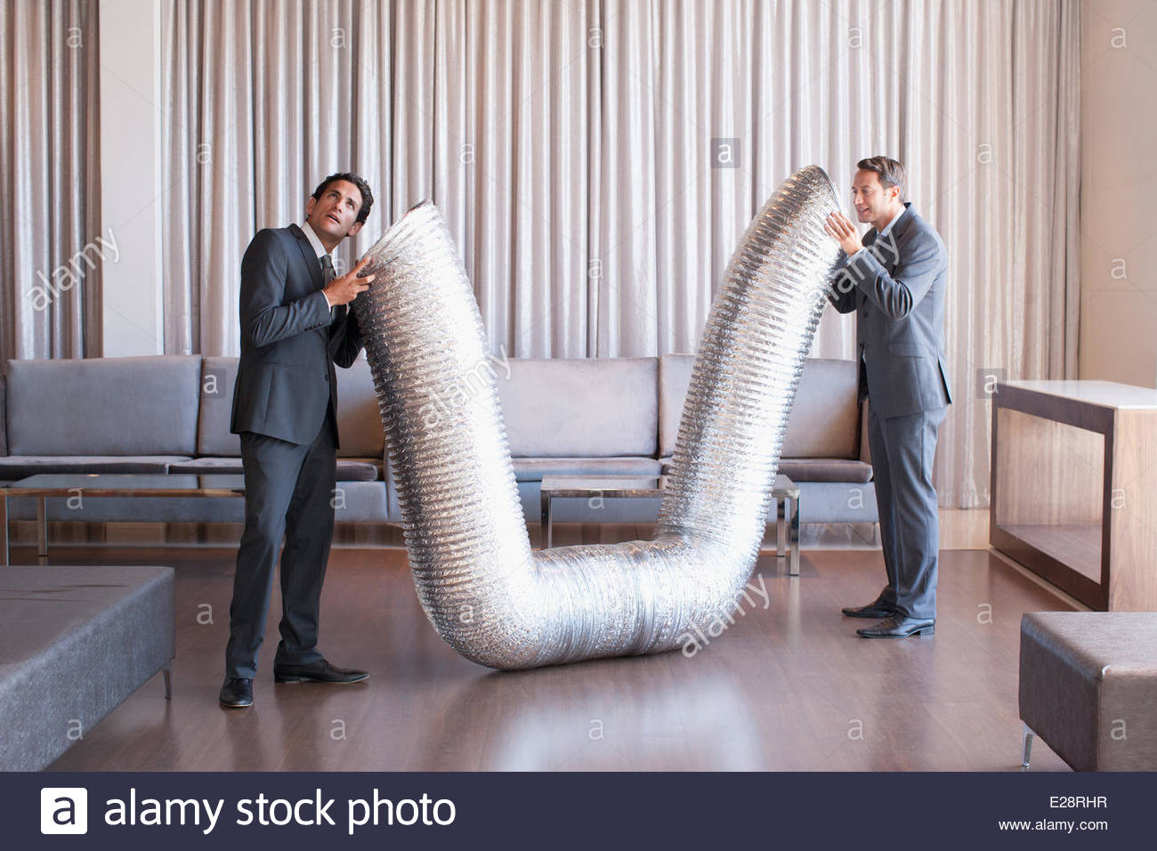 Business people holding metal tubing in hotel lobby - Stock Image