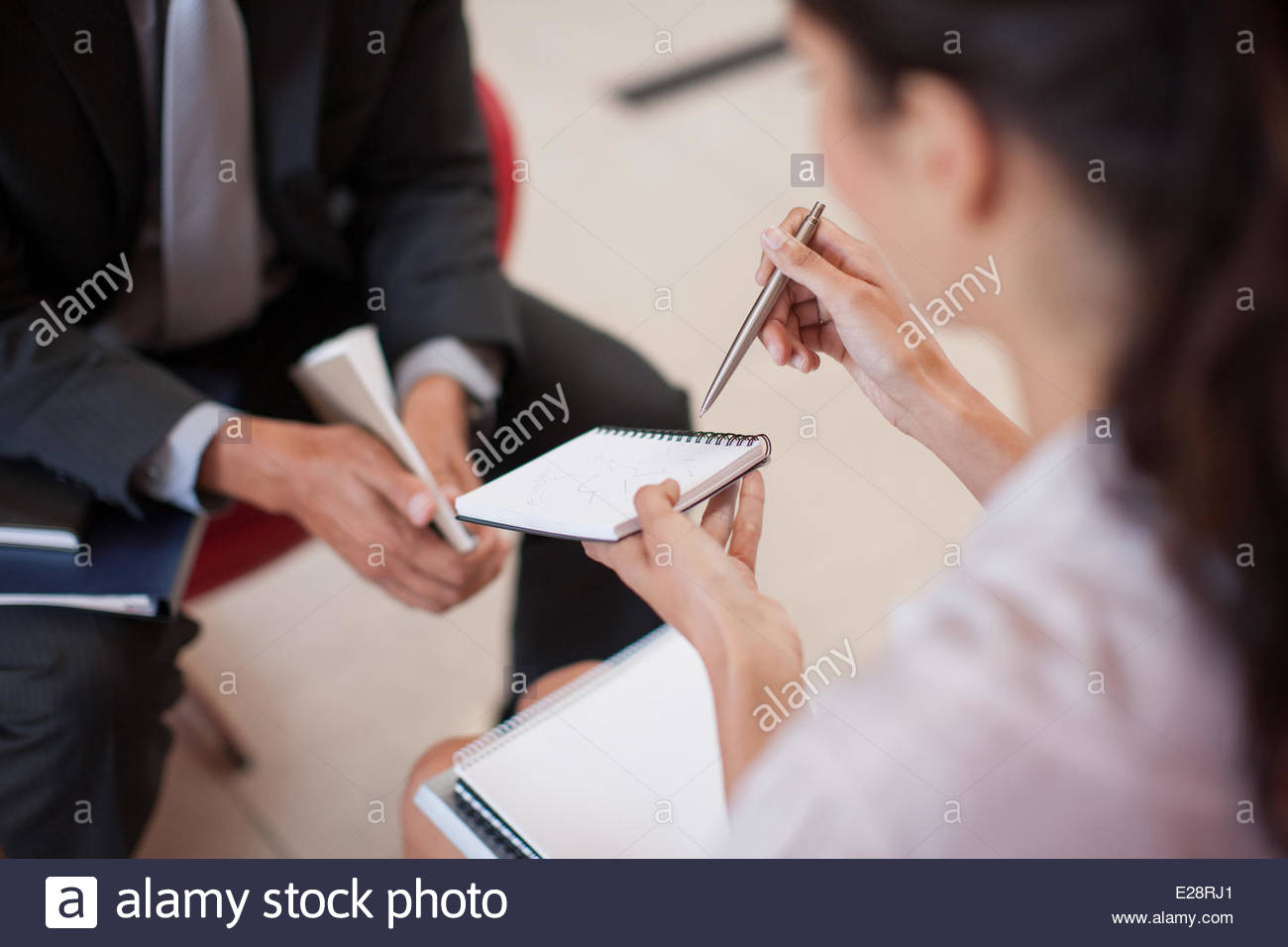 Business people looking at notebook in office - Stock Image