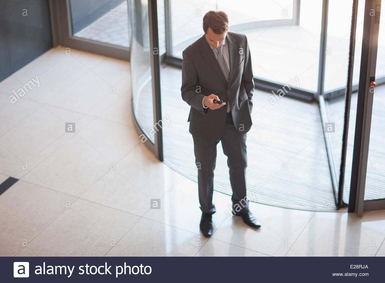 Businessman holding cell phone near revolving doors Stock Photo