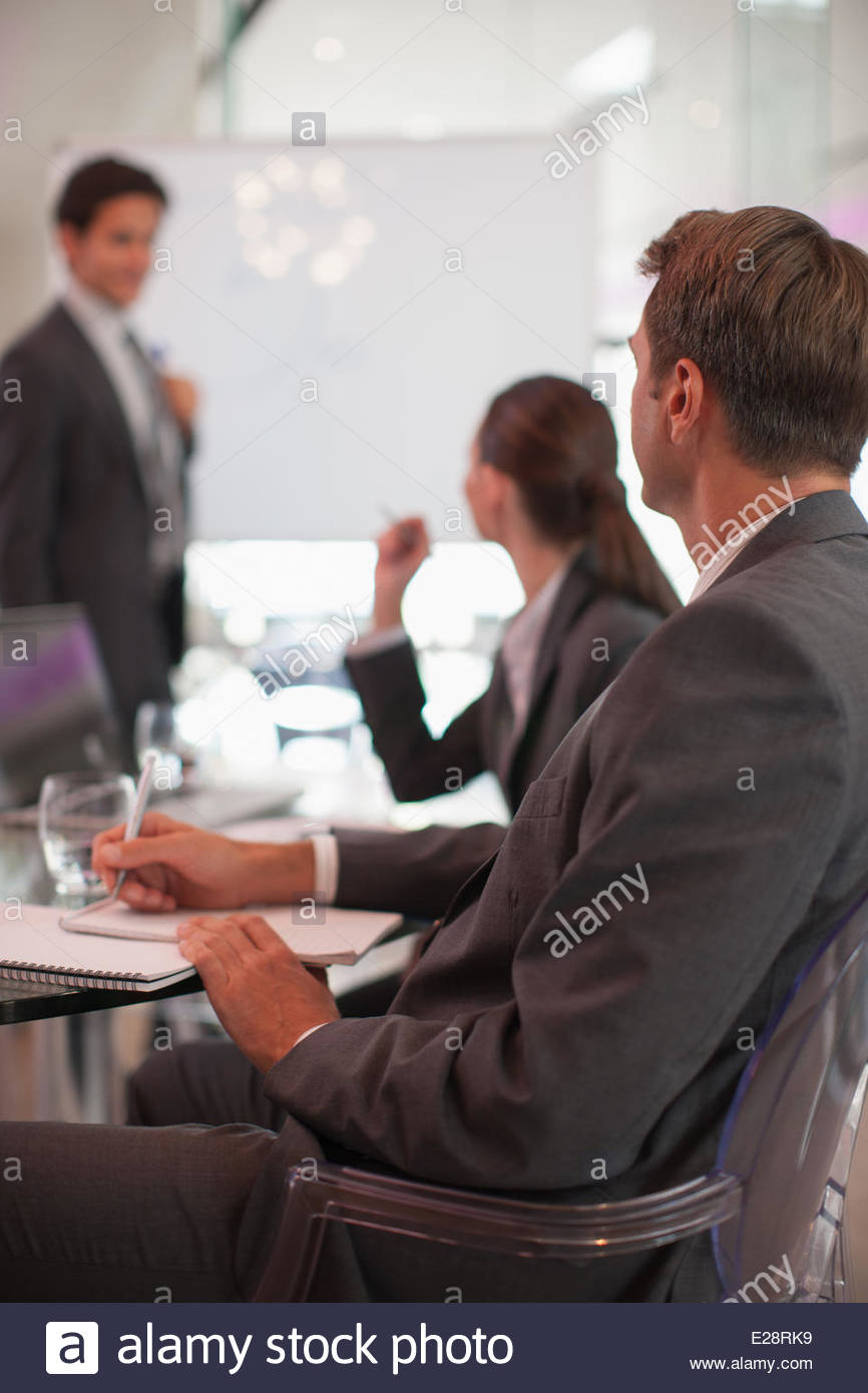 Businessman talking to co-workers in conference room - Stock Image