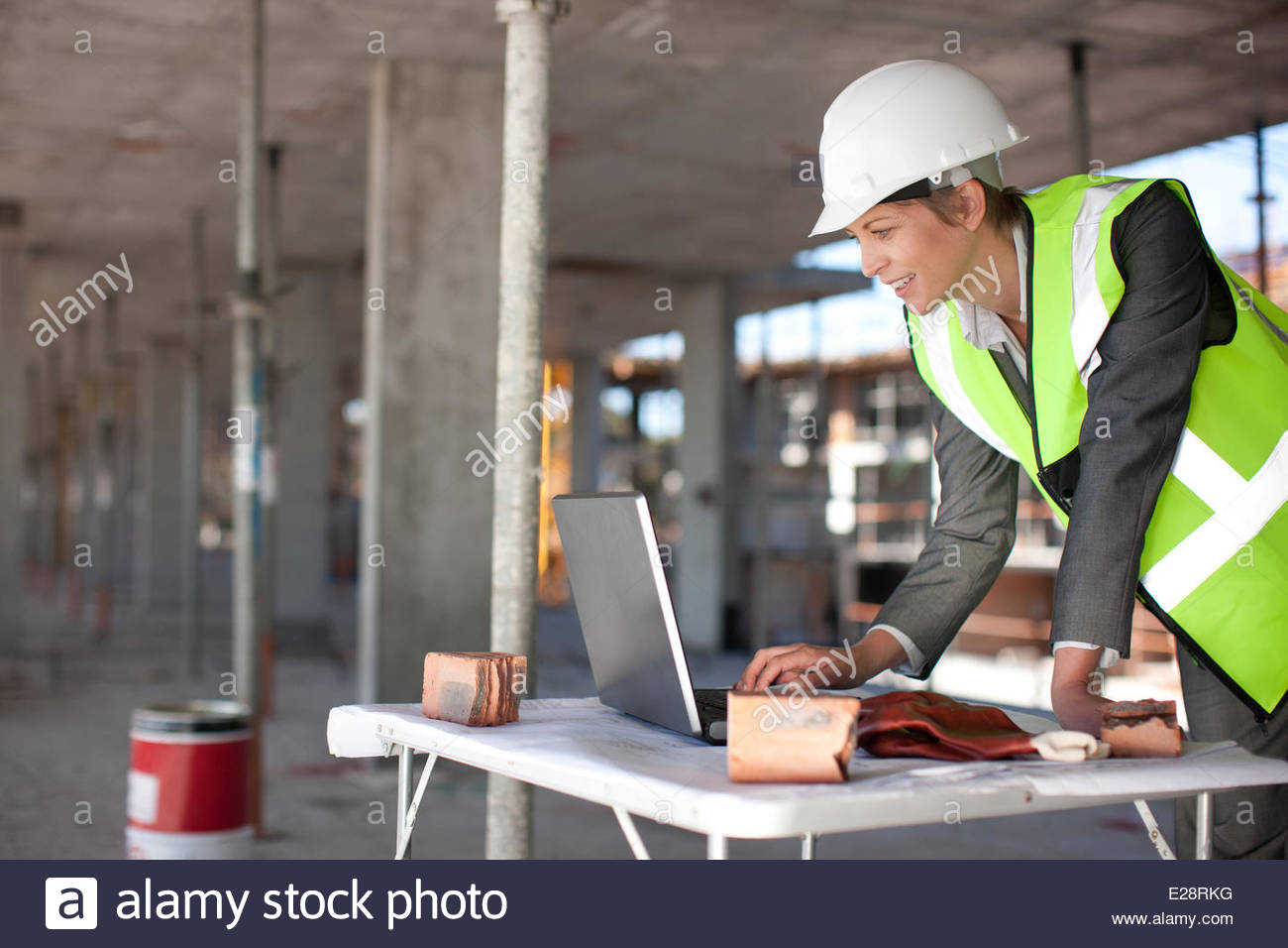 Construction worker using laptop on construction site - Stock Image