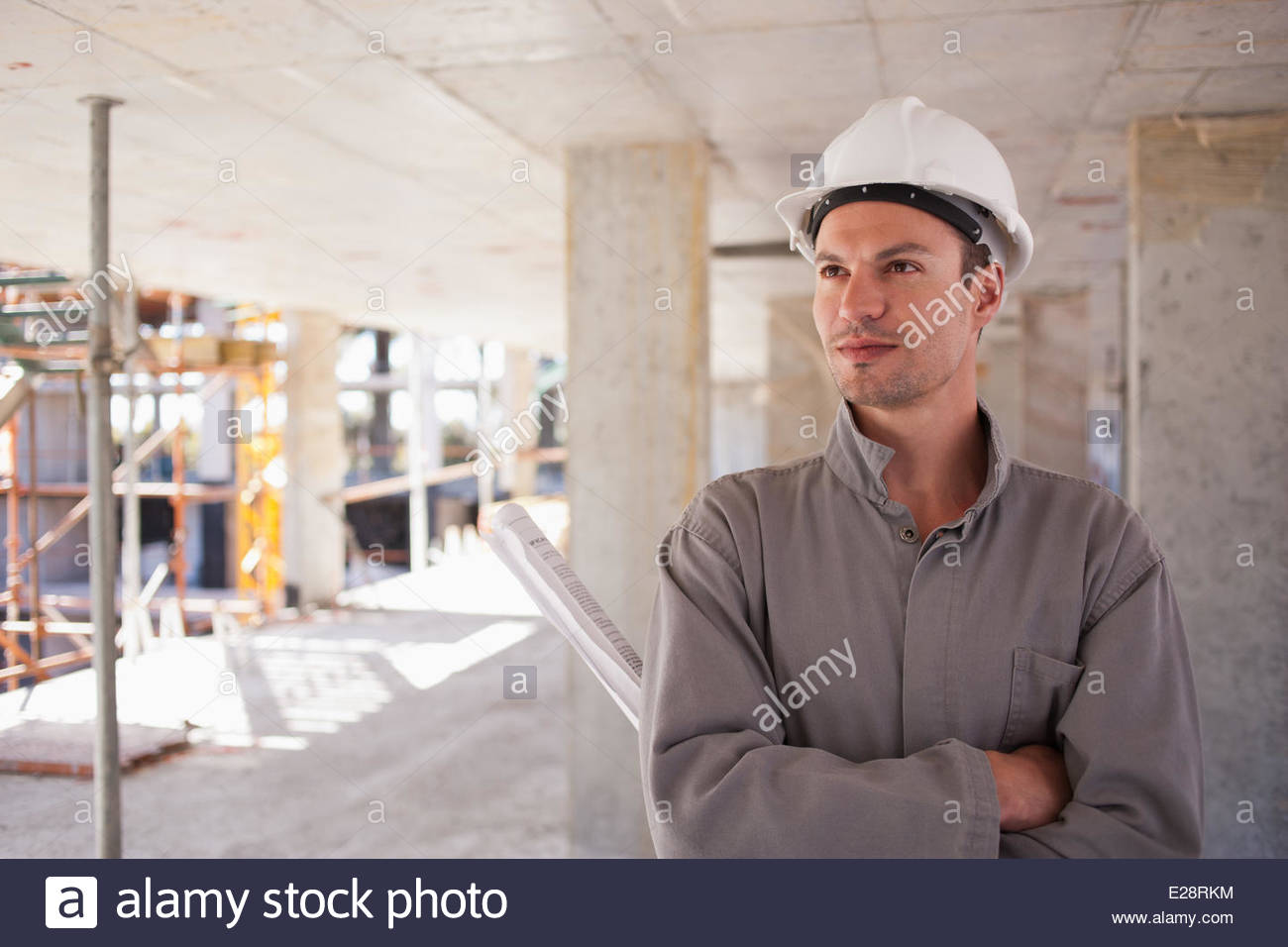 Construction worker with arms crossed on construction site - Stock Image