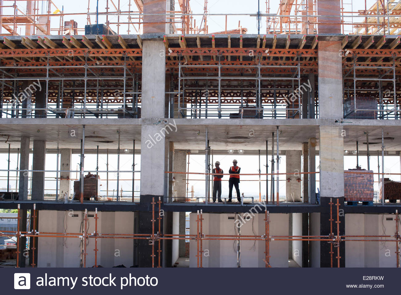 Construction workers standing on construction site - Stock Image