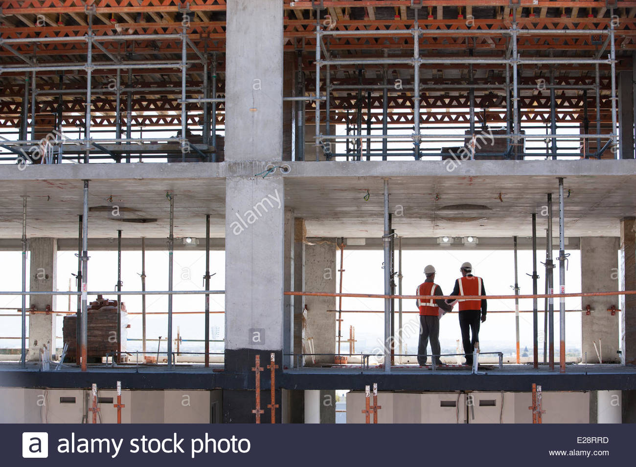 Construction workers standing together on construction site - Stock Image