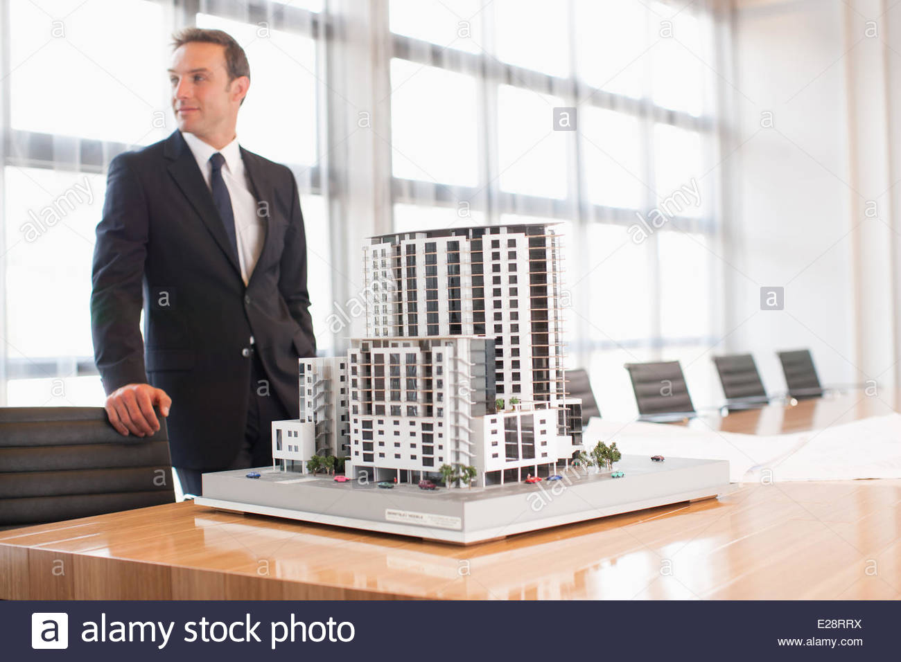 Businessman standing in conference room with model building - Stock Image