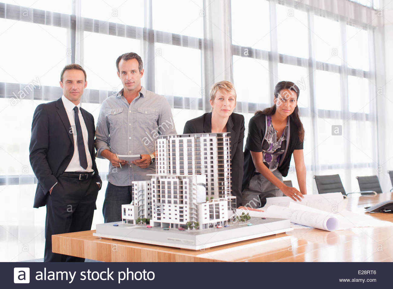Business people standing with building model - Stock Image