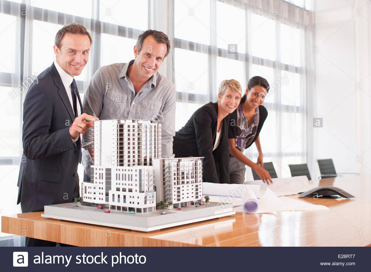 Business people looking at blueprints and model building - Stock Image