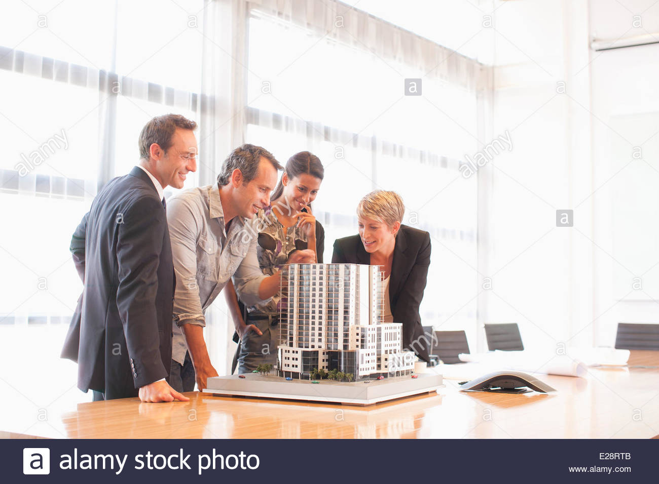 Business people looking at model building in conference room Stock Photo