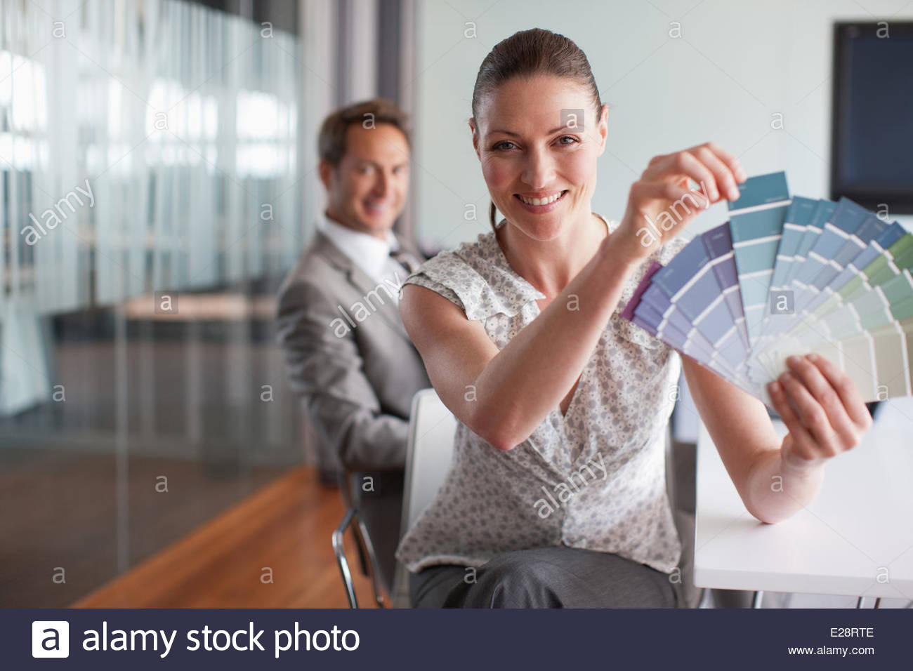 Businesswoman holding color swatches in conference room - Stock Image