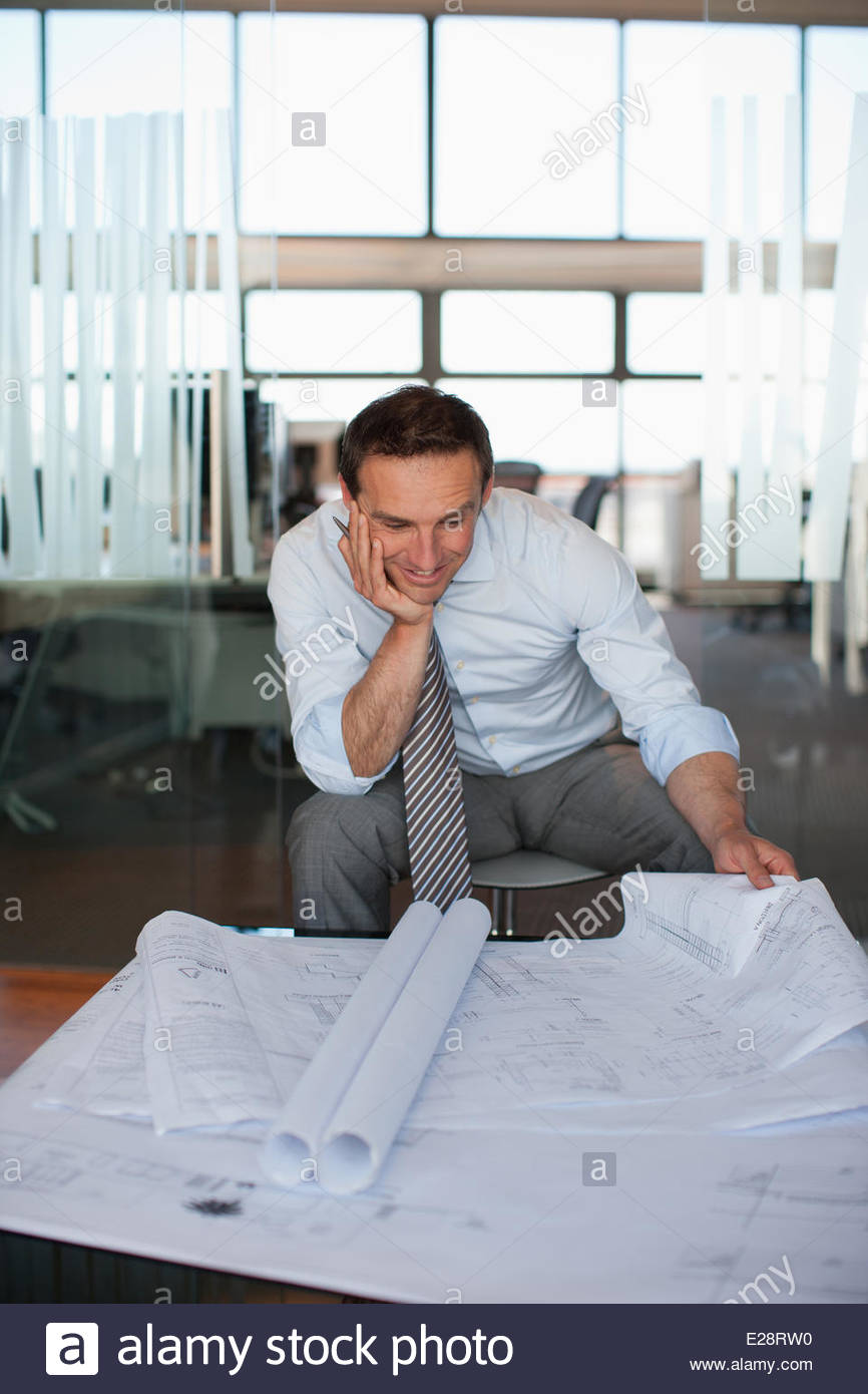 Architect reviewing blueprints in office - Stock Image