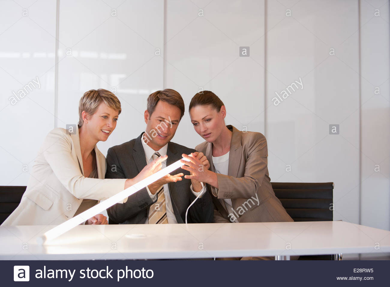 Business people looking at glowing light - Stock Image